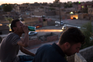 16/09/2016 - Snuny, Iraq: Saadon and his friend Najiman sit on the roof of an uncle´s house in Snuny and drink beers. He isn´t able to visit Sinjar often since his family was displaced.